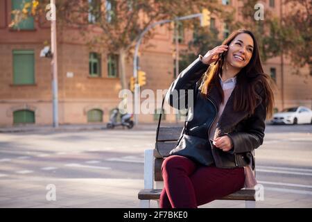 joyeuse jeune femme assise sur un banc de rue riant tout en faisant un appel téléphonique, concept de communication et de style de vie urbain, copyspace pour le texte