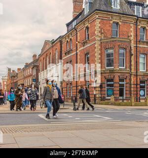 Les personnes portant un masque de visage traversent une route et d'autres suivent. Il y a un bâtiment en brique rouge d'un côté et un ciel nuageux au-dessus.