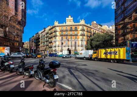 Trafic urbain dans la rue entre les bâtiments sous ciel bleu à Barcelone - capitale et plus grande ville de Catalogne, Espagne.