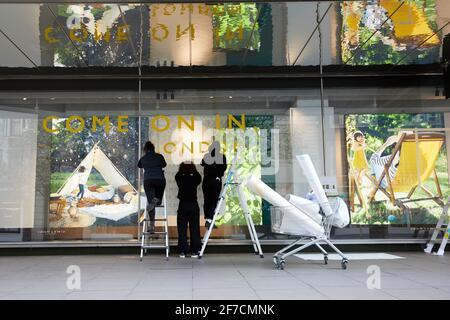 Londres, Royaume-Uni - 6 avril 2021 : les employés du magasin John Lewis d'Oxford Street apposent des panneaux pour accueillir les clients avant que les règles de la feuille de route de confinement en Angleterre permettent aux magasins de rouvrir le 12 avril. Banque D'Images