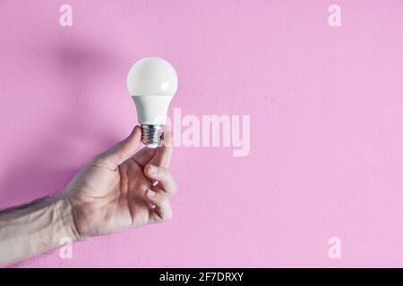 Main d'un jeune adulte tenant une ampoule à économie d'énergie sur fond de mur rose. Concept de créativité, d'efficacité et de durabilité.