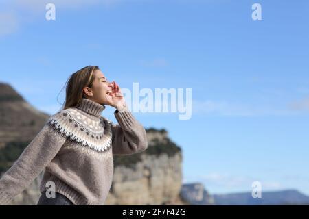 Vue latérale d'une femme heureuse criant pour l'écho en montagne en hiver