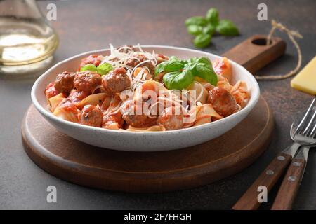 Pâtes fetuccine avec boulettes de viande, parmesan, tomates, basilic sur fond brun. Gros plan.