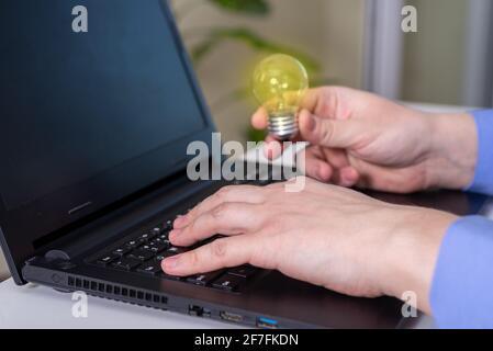 Gros plan d'UNE femme d'affaires tenant une ampoule lumineuse dans le bureau. Idée de concept.
