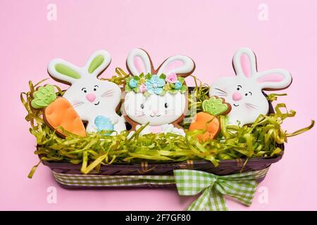 Biscuits au sucre de Pâques décorés de glaçage coloré sous forme de lapins blancs et de carottes orange. Panier en bois avec décoration de Pâques sur fond pastel.