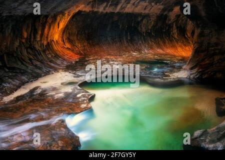Une lumière réfléchissante illumine les parois du canyon de la fente en labyrinthe du Subway avec ses piscines émeraude dans le parc national de Zion.