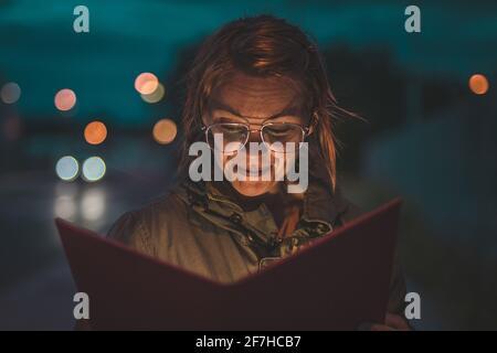 Une femme avec des lunettes rétro est en cours de lecture d'un livre rouge pendant la nuit dehors. Concept de mauvais éclairage lors de la lecture, faible éclairage rend vos yeux tir