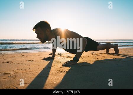 Jeune homme en forme faisant des push-up ou de l'exercice sur le plage au lever du soleil