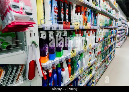 Un assortiment de poudres à laver de différentes marques sur les étagères du magasin.
