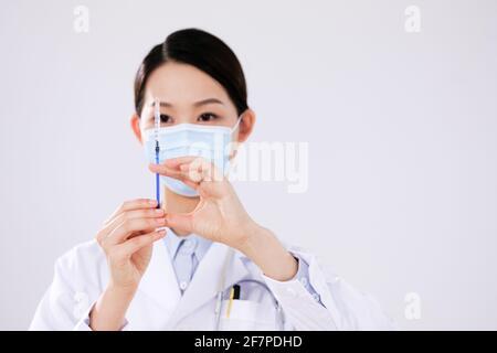 Une femme médecin avec un masque utilise un front de seringue vue