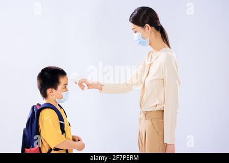 Le petit garçon a pris sa température avant l'école par son maman