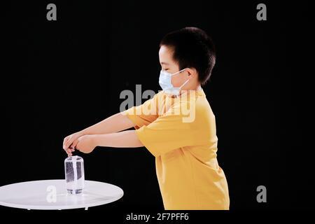 Un petit garçon avec un masque utilise un désinfectant pour les mains