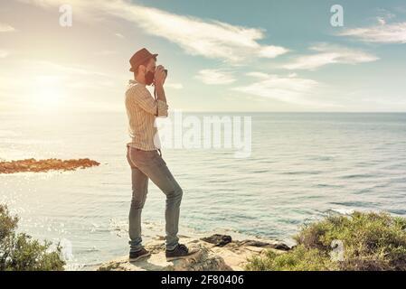 Un jeune voyageur prend une photo d'un coucher de soleil à l'intérieur face à la mer tout en marchant avec un masque dû à la nouvelle normale imposée par le covid
