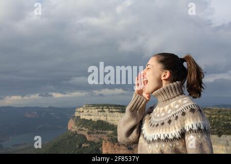 Profil d'une femme criant dans la montagne en hiver vacances