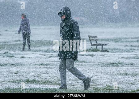 WIMBLEDON LONDRES, ROYAUME-UNI 12 AVRIL 2021. Les gens sont pris dans une lourde douche à neige sur Wimbledon Common un matin froid avec des températures glaciales. Credit amer ghazzal/Alamy Live News Banque D'Images