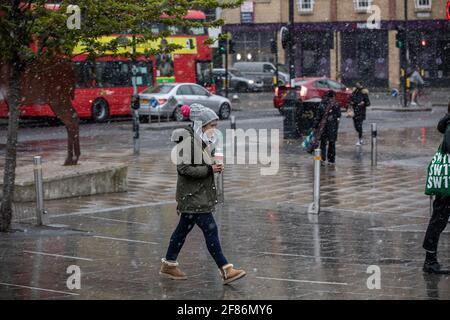 Londres, Royaume-Uni. 12 2021 avril : les voyageurs se mettent en route pour traverser un étonnant blizzard de neige printanier à Wimbledon le premier jour, les restrictions du coronavirus sont levées en Angleterre pour permettre aux gens de se couper les cheveux et de manger et boire à l'extérieur des pubs et des restaurants. 12 avril 2021 Wimbledon, Angleterre. Crédit : Jeff Gilbert/Alamy Live News Banque D'Images