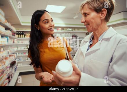 Femme achetant des médicaments en pharmacie demandant la posologie à un pharmacien principal en vous tenant près des tablettes