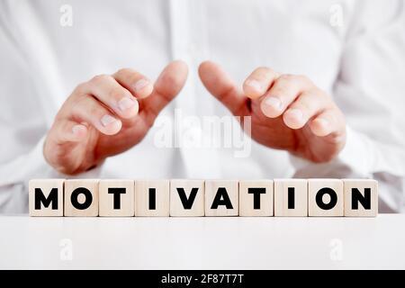 Homme d'affaires tenant ses mains sur les cubes de bois avec le mot motivation. Concept d'entreprise.