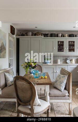 Cuisine de style Shaker avec bancs Gustavian et sol travertin dans les années 1930 West Sussex rénovation côtière.