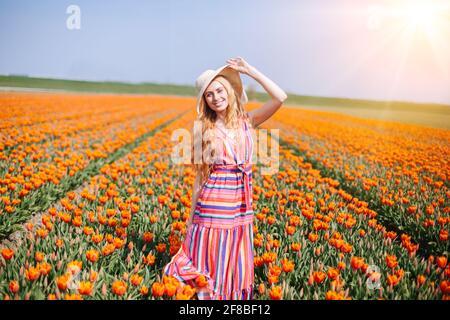 Belle femme à cheveux rouges vêtue d'une robe à rayures debout sur des champs de fleurs de tulipe colorés dans la région d'Amsterdam, Hollande. Paysage hollandais magique avec champ de tulipe. Concept Trevel et Spring.