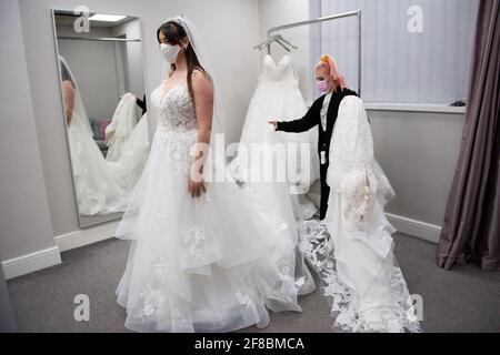 Mariée-à-être Erin Barwell tente sur des robes pour la première fois depuis que les détaillants non essentiels ont rouvert cette semaine. Erin, de Stoke-on-Trent, doit se marier en février prochain et a essayé des robes à la mariée de Roberta à Burslem, Stoke-on-Trent, suite à l'assouplissement supplémentaire des restrictions de verrouillage en Angleterre. Date de la photo: Mardi 13 avril 2021.