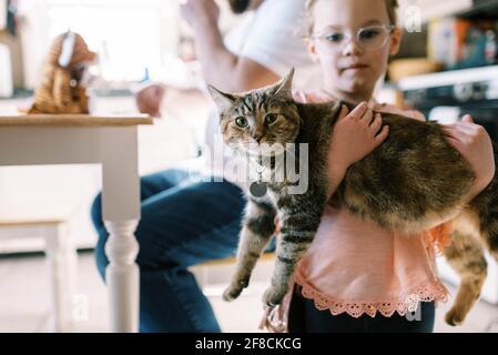 Petite fille tenant son chat animal mignon dans elle les bras dans la cuisine