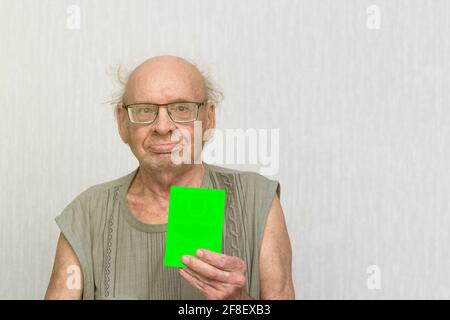 Vieux bald retraité avec lunettes en chemise grise est vide dans sa main.