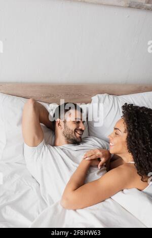 heureux couple interracial regardant l'un l'autre dans le lit
