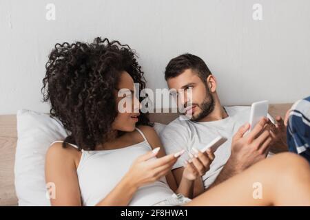 un couple interracial mécontent tenant un téléphone portable et se regardant l'un l'autre dans la chambre