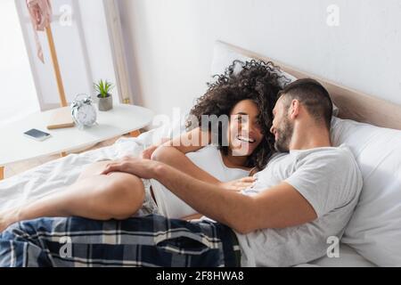 couple interracial gai souriant et allongé sur le lit