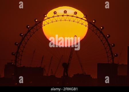 Londres, Royaume-Uni. 14 avril 2021. Météo au Royaume-Uni : coucher de soleil spectaculaire au-dessus de la roue London Eye alors que la ville se prépare à une mini-vague de chaleur. Credit: Guy Corbishley/Alamy Live News