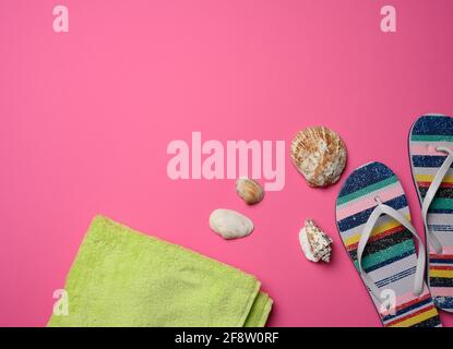 pantoufles multicolores pour femmes et seashell sur fond rose, vue du dessus