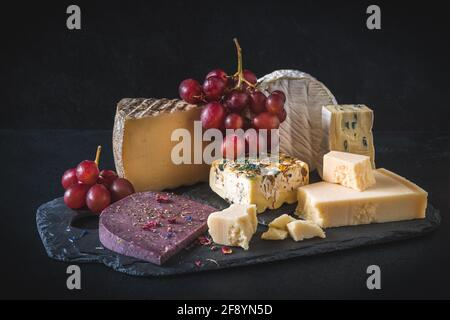 Variété de fromages exclusifs et colorés, décorés de raisins rouges, sur fond noir
