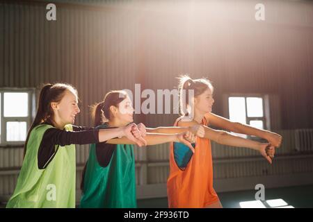 Les gens, les femmes d'amitié sportives, les fans de football, la salle de gym intérieure, soutiennent l'équipe favorite avec le ballon de football montrant le pouce vers le bas, lumière du soleil.