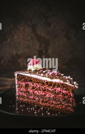 Morceau de torte de chocolat framboise sur une plaque noire sur fond marron foncé, vertical avec espace de copie