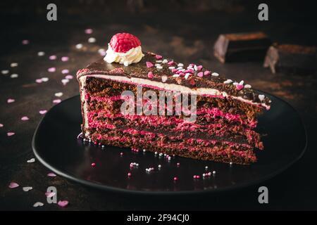 Morceau de torte de chocolat à la framboise sur une assiette noire sur arrière-plan marron foncé