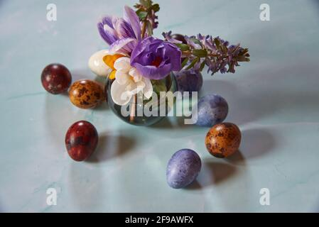 Un petit vase avec des fleurs printanières et des œufs de Pâques peints sur un fond clair.