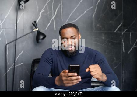 Homme africain masculin concentré assis sur un canapé regardant l'écran de cellule en attente de récompense dans le prix d'argent de jeu d'emploi, main dans un poing, lit des nouvelles se préoccupant de la situation dans le pays ou le monde