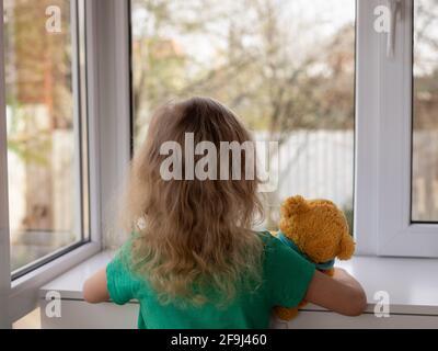 une petite fille avec son ours en peluche regarde par la fenêtre du jardin. concept de rester à la maison. foyer sélectif