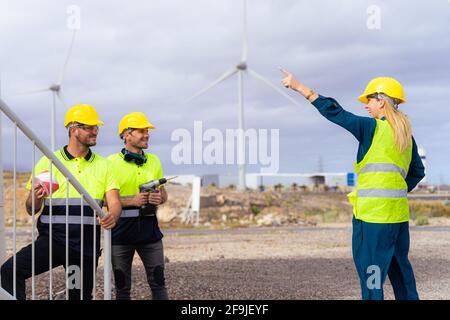 Deux travailleurs qualifiés écoutent les explications de la femme ingénieur au sujet des nuances de travail. Énergie renouvelable et concept professionnel.