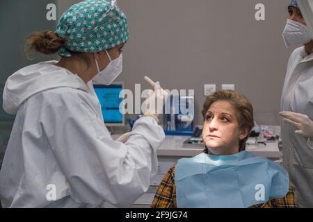 femme dentiste en cabinet dentaire discutant avec la patiente et se préparant au traitement.