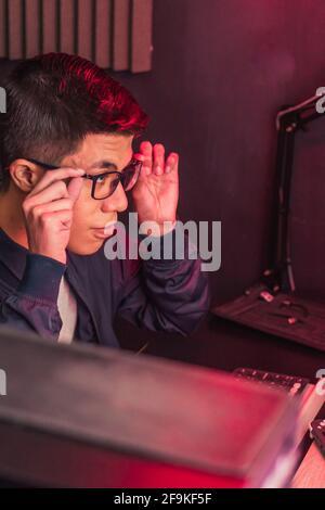 Jeune homme faisant différentes tâches sur son ordinateur. Création de contenu multimédia à afficher sur leurs réseaux sociaux.