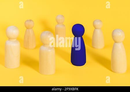 Figure en bois bleu parmi de nombreuses figures jaunes. Se démarquer de la foule, individualité, leadership, être unique idée minimale