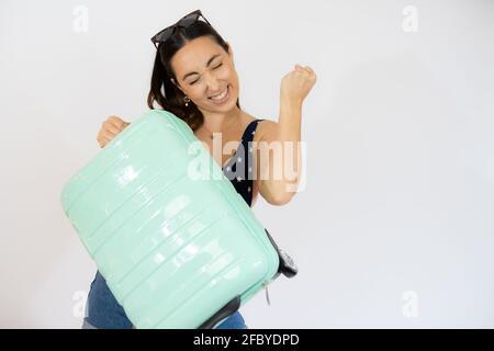 Jeune voyageur femme tenant une valise levant poing après une victoire, gagnant concept. Isolé sur fond blanc