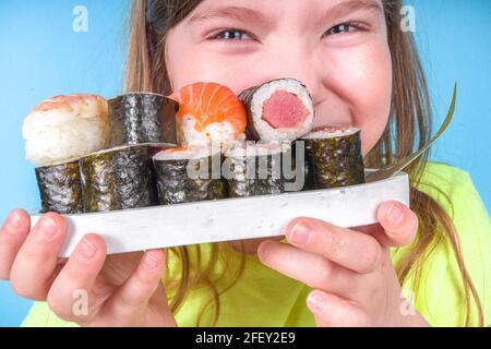 Une petite fille adorable aime manger des sushis. Joyeux drôle caucasien blonde petite fille avec divers rouleaux de sushi et baguettes. Sur fond bleu vif