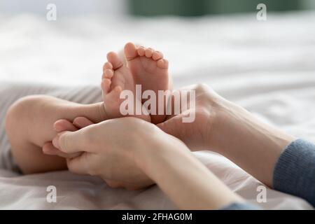 Soins aux mères. Gros plan de maman aimante tenant les pieds du nouveau-né dans les mains