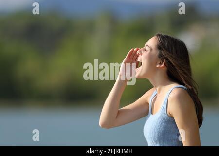 Profil d'une femme hurlant dans un lac l'été