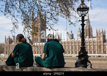 Londres, Royaume-Uni, 27 avril 2021 : les médecins étudiants Charlie et Surina prennent une pause au-dessus du mur commémoratif national Covid alors que le Premier ministre Boris Johnson est toujours accusé d'avoir préféré que les « corps s'accumulent » plutôt que d'avoir un troisième verrouillage. Avec un coeur dessiné pour chacun des plus de 150,000 personnes qui sont mortes dans la pandémie de coronavirus au Royaume-Uni, le mémorial s'étend le long du mur de l'hôpital St Thomas, en face du Parlement sur la rive opposée de la Tamise. Anna Watson/Alay Live News