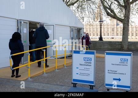 Londres, Royaume-Uni, 27 avril 2021 : les gens font la queue à l'endtrance vers un centre de vaccination situé sur le terrain de l'hôpital St Thomas, en face du Parlement, sur la rive opposée de la Tamise. Le Premier ministre Boris Johnson est toujours accusé d'avoir préféré que les « corps s'accumulent » plutôt que d'avoir un troisième verrouillage. Anna Watson/Alay Live News