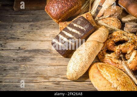 Assortiment de délicieux pains fraîchement sortis du four, sur fond de bois rustique copie espace